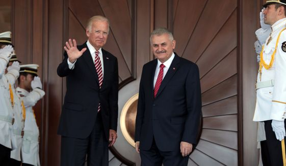 Vice President Joe Biden waves after he was greeted by Turkish Prime Minister Binali Yildirim on Wednesday in Ankara. (Associated Press)