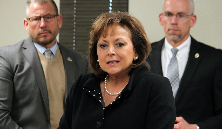 FILE - This Tuesday, Jan. 5, 2016 file photo, Gov. Susana Martinez, center, unveils her budget priorities for the upcoming legislative session as Corrections Secretary Greg Marcantel, left, and Public Safety Secretary Greg Fouratt stand behind her during a news conference in Albuquerque, N.M. New Mexico officials are revising revenue expectations downward as state lawmakers confront state budget shortfalls reminiscent of the 2008 recession. Members of the Legislative Finance Committee that drafts the state budget are meeting Wednesday, Aug. 24, 2016, in the town of Red River. Martinez says she plans to reconvene lawmakers and has recommended all state agencies reduce spending by 5 percent. (AP Photo/Susan Montoya Bryan, File)
