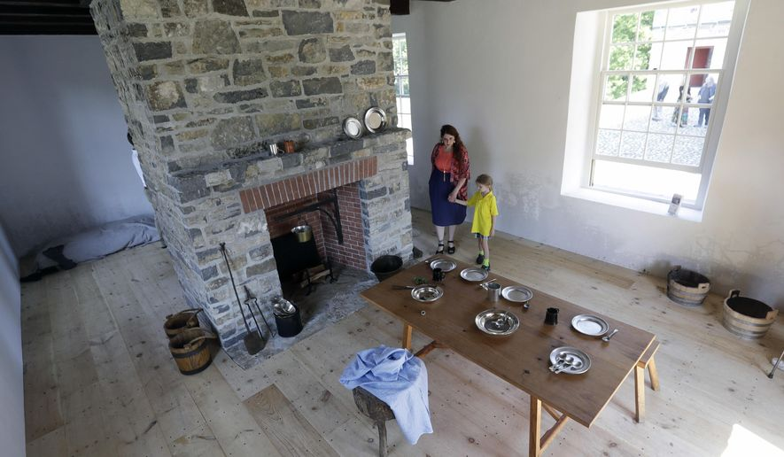 Bernadette Weaver, of the Friends of Johnson Hall, and her son Tavin walk inside a restored stone house at Johnson Hall State Historic Site, Wednesday, Aug. 24, 2016, in Johnstown, N.Y. State and local officials marked the restoration of the historic building at the Colonial-era site in the Mohawk Valley. Johnson Hall was the estate of Sir William Johnson, an Irish immigrant who was one of the wealthiest and most influential men in North America before the Revolutionary War. (AP Photo/Mike Groll)