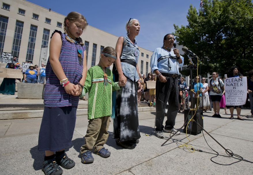 Members of the Lakota people, Timothy Swallow, right, his wife Karan, second from right, and their children Naimah, 8, and Tas, 6, sing the native spiritual song during a rally outside the US District Court in Washington, Wednesday, Aug. 24, 2016, in solidarity with the Standing Rock Sioux Tribe in their lawsuit against the Army Corps of Engineers to protect their water and land from the Dakota Access Pipeline. A federal judge in Washington considered a request by the Standing Rock Sioux for a temporary injunction against an oil pipeline under construction near their reservation straddling the North Dakota-South Dakota border. The Sioux are challenging the Army Corps of Engineers' decision to grant permits for the $3.8 billion pipeline that is intended to carry oil from North Dakota to Illinois. (AP Photo/Manuel Balce Ceneta)