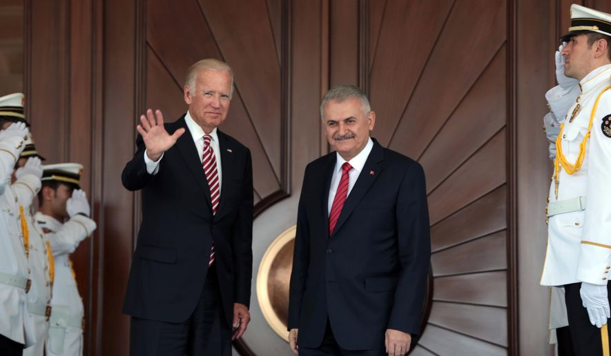U.S Vice President Joe Biden, left, waves after he was greeted by Turkish Prime Minister Binali Yildirim in Ankara, Turkey, Wednesday, Aug. 24, 2016. Biden has arrived in Ankara for talks with Turkish leaders as Turkey launched a military operation to clear a Syrian border town of Islamic State militants. The visit comes at a difficult time for ties between the two NATO allies.(AP Photo/Burhan Ozbilici)
