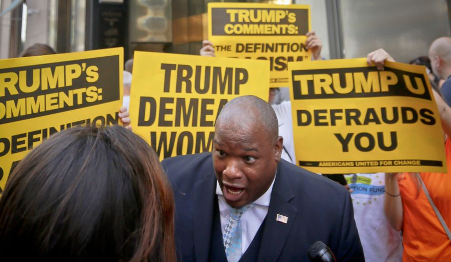 Donald Trump supporter Mark Burns, an evangelical pastor from South Carolina, is surrounded by by vocal anti-Trump protesters during an interview before attending a meeting between minority Republicans and Presidential candidate Trump, Thursday Aug. 25, 2016, in New York. (AP Photo/Bebeto Matthews)