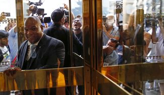 Pastor Mark Burns enters Trump Tower as protestors yell at him from outside, as Republican presidential candidate Donald Trump holds a roundtable meeting with the Republican Leadership Initiative in his offices at Trump Tower in New York, Thursday, Aug. 25, 2016. (AP Photo/Gerald Herbert)