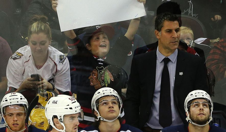 A young Lake Erie Monsters fan holds up his sign behind the Monsters bench with coach Jared Bednar standing at right wearing a jacket and tie during a game against the Iowa Wild on Oct. 16, 2015, at Quicken Loans Arena in Cleveland. The Colorado Avalanche have hired Jared Bednar as their new head coach. (Chuck Crow/The Plain Dealer)