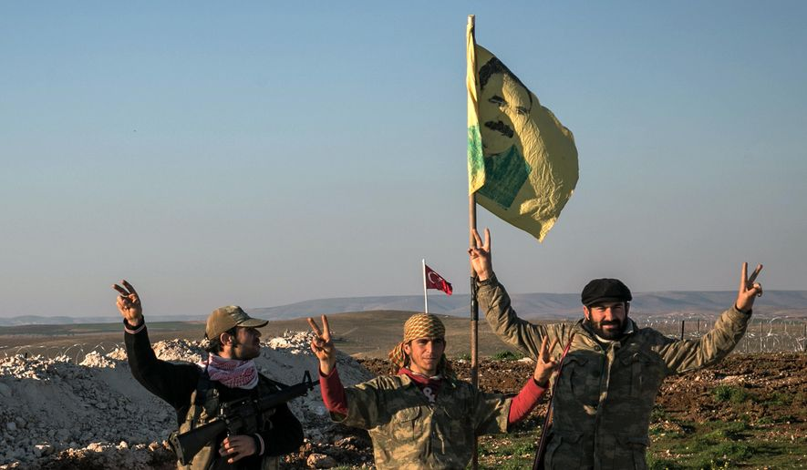 Syrian Kurdish militia members of the YPG make a V-sign next to a drawing of Abdullah Ocalan, jailed Kurdish rebel leader, in Esme village in Aleppo province, Syria, in this Feb. 22, 2015, file photo. (Mursel Coban/Depo Photos via AP, File)