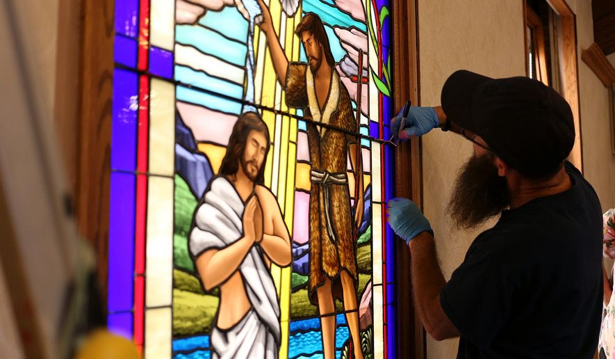 Ruben Llano  works on the installation of a handmade glass window at the Addison Congregational Church, Thursday, Aug. 25, 2016, in Addison Mich. (Samantha Madar/Jackson Citizen Patriot via AP)