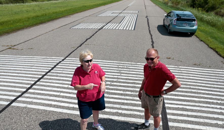 FOR RELEASE SATURDAY, AUGUST 27, 2016, AT 12:01 A.M. CDT.- Patti Bruha, left, a student of certified flight instructor and former airport manager Henry Peterson, right, talks about the closing of Joshua Sanford Field, a small airport in Hillsboro, Wis., Wednesday, Aug. 10, 2016. The two, who were advocates of the airport's continued operation, stand on runway 5/23 during an interview.  Those who land at the city-owned airstrip are asked to sign in on a faded yellow legal pad protected by Plexiglas in a self-serve kiosk constructed by Ian Collins, an Eagle Scout with Boy Scout Troop 83, Wisconsin State Journal  reported. The plaque doesn't say in what year Collins built the structure. (M.P King/Wisconsin State Journal via AP)