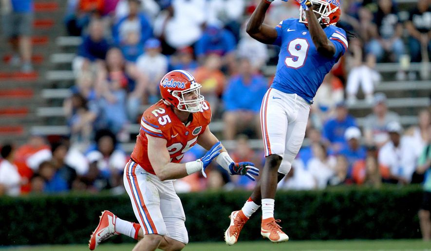 In this April 8, 2016, file photo, Florida receiver Dre Massey jumps to make a catch in front of Florida linebacker Matt Rolin during a spring football game in Gainesville, Fla. Massey is Florida's most versatile player, capable of lining up at receiver, running back, quarterback, returner and punter. Yes, punter.The 25th-ranked Gators probably won't ask Massey to kick, but they do expect the junior college transfer to be a huge help on offense this season.(Matt Stamey/The Gainesville Sun via AP, File)