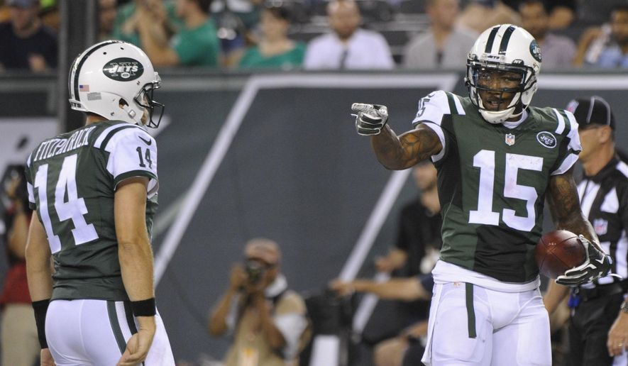 """FILE - In this Friday, Aug. 21, 2015 file photo, New York Jets wide receiver Brandon Marshall (15) gestures to quarterback Ryan Fitzpatrick (14) after they scored on a two point conversion during the first half of a preseason NFL football game against the Atlanta Falcons in East Rutherford, N.J. Marshall knew very little about Fitzpatrick when they became teammates last offseason. And then, he saw Fitzpatrick throw. """"He was terrible,"""" a smiling Marshall said. (AP Photo/Bill Kostroun, File)"""