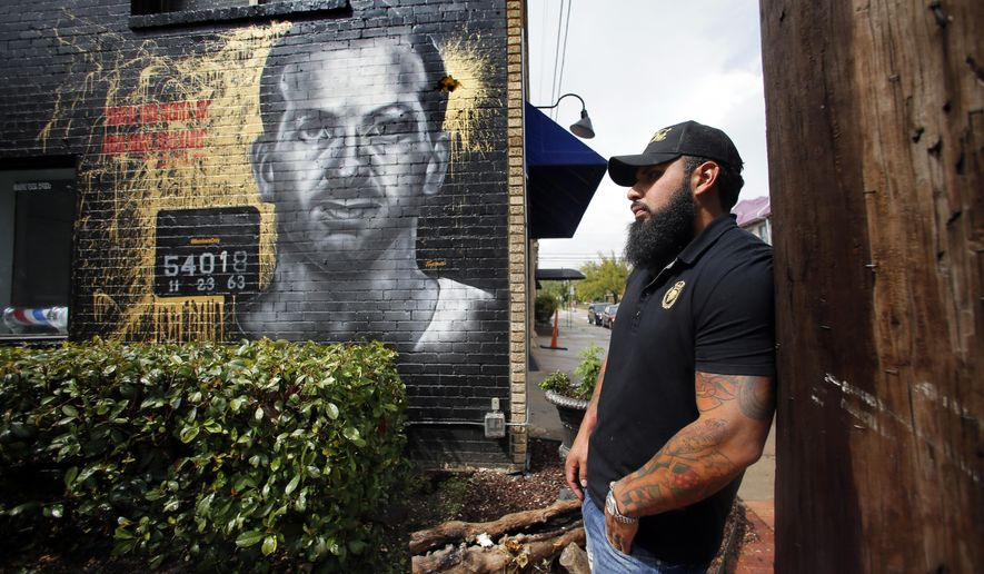 Christian Avanti, owner of the Members Only barbershop, poses in front of a mural of Lee Harvey Oswald painted on an exterior wall outside his business, Friday, Aug. 26, 2016, in Dallas. A nearly two-story mural of assassin Lee Harvey Oswald recently painted on a Dallas building is drawing criticism for being insensitive. (AP Photo/Tony Gutierrez)