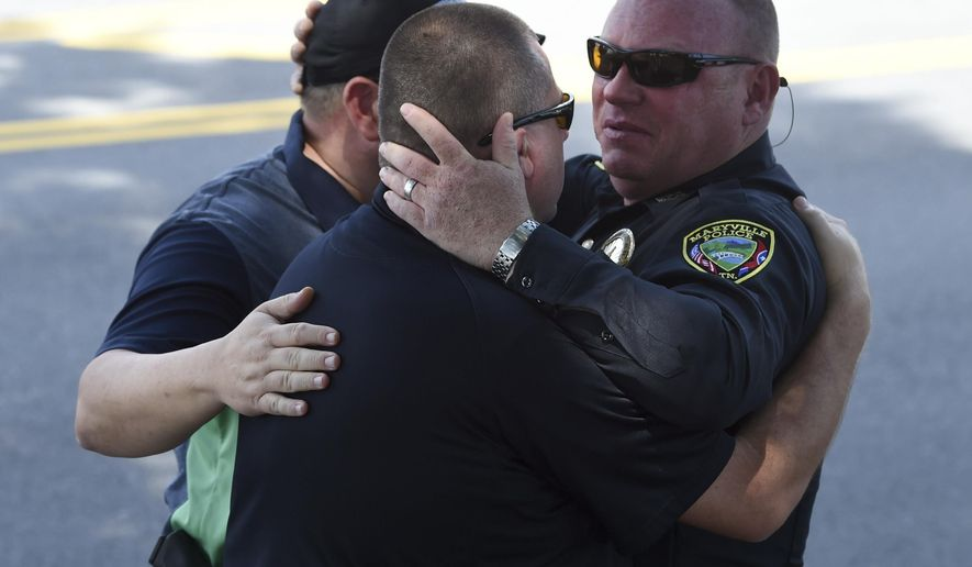 Maryville Police Department Detective John Foley, right, hugs Blount County Sheriff's Office investigators Andy Waters, center, and Joey Parton after the body of slain police officer Kenny Moats passed in a procession Friday, Aug. 26, 2016, in Maryville, Tenn. The nine-year veteran officer was killed Thursday after he was shot while answering a domestic violence call. Brian Keith Stalans, 44, was taken into custody after the shooting and is being held for investigation pending charges that will likely be placed Friday, according to the Blount County Sheriff's Office. (Amy Smotherman Burgess/Knoxville News Sentinel via AP)