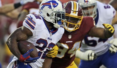 Buffalo Bills running back Reggie Bush, left, tries to get away form Washington Redskins defensive end Preston Smith (94) during the first half of an NFL preseason football game Friday, Aug. 26, 2016, in Landover, Md. (AP Photo/Mark Tenally)
