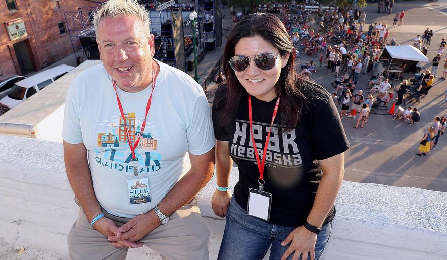 ADVANCE FOR WEEKEND EDITIONS AUG. 27-28 - In this Aug. 18, 2016 photo Brett Lindner, left, and Sharena Anser sit together on the rooftop of Prairie Pride Brewing Co. as fans gather for the Hear Nebraska concert series in Grand Island. Neb. (Andrew Carpenean/The Independent via AP)