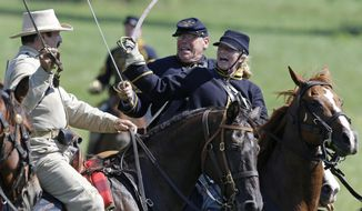 In this June 29, 2013, file photo, reenactors demonstrate a cavalry battle to commemorate the 150th anniversary of the Battle of Gettysburg at Bushey Farm in Gettysburg, Pa.  (AP Photo/Matt Rourke, File) ** FILE **