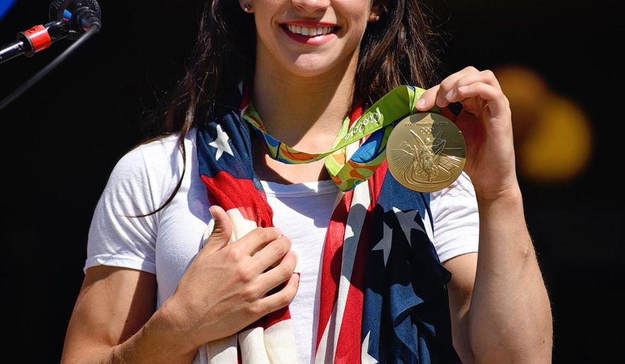 Aly Raisman, U.S. Olympic gold medalist in gymnastics, shows off her gold medal to her hometown of Needham, Mass. in a rally at town hall, Saturday, Aug. 27, 2016. (Faith Ninivaggi/The Boston Herald via AP)