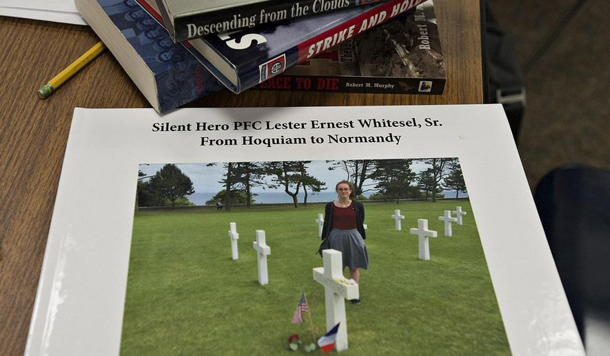 ADVANCE FOR WEEKEND EDITIONS, AUG. 17-18 - This Aug. 15, 2016 photo, shows the cover of a book about Ally Orr's project in Vancouver, Wash., with a photo of Orr at the grave of Pfc. Lester Whitesel Sr. in a cemetery overlooking Omaha Beach in France. The high school student has created a salute to the life and times of a soldier who parachuted into France as part of the D-Day invasion. (Amanda Cowan/The Columbian via AP)
