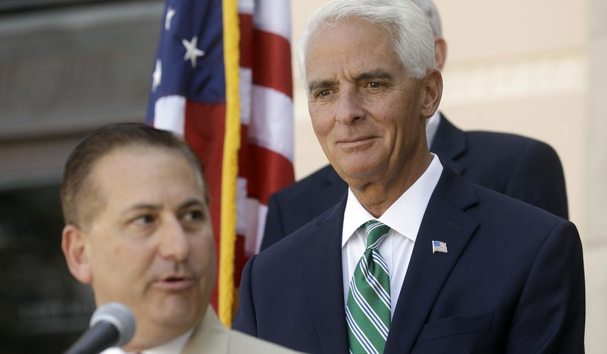 In this Aug. 17, 2016 photo, former Florida Gov. Charlie Crist, right, listens to St. Petersburg Mayor Rick Kriseman during a news conference in St. Petersburg, Fla. Crist is running as a democrat for the U.S. House of Representatives for the 13th District in Florida. (AP Photo/Chris O'Meara)