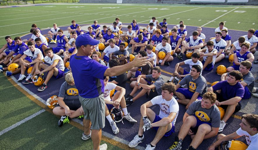 """Denham Springs High School football coach Dru Nettles talks to his team at the start of the team's first practice after the flood in Denham Springs, La., Wednesday, Aug. 24, 2016. Nettles sat the team down on the purple logo at midfield and asked his players if they saw the aerial photographs of their inundated school. """"If you look at the back of campus, the one thing that didn't go underwater was this logo,"""" Nettles said. """"Awesome sign right there that this 'DS' was shining ... to give people hope."""" (AP Photo/Max Becherer)"""