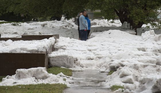 """Hail as deep as two feet lies in the front yards of home along Logan Avenue between Platte Avenue and Bijou Street after a storm hit Colorado Springs, Colo., Monday, Aug. 29, 2016.  Colorado Springs has dispatched snow plows to clean up after a powerful storm dumped heavy hail across the city. City spokeswoman Kim Melchor tells The Gazette she does not know how many plows were sent out, but crews are """"pretty busy"""" after Monday afternoon's storm. (Christian Murdock/The Gazette via AP)"""