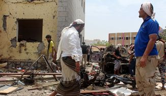 Fighters loyal to the government gather at the site of a suicide car bombing in Yemens southern city of Aden, Yemen, Monday, Aug. 29, 2016. The bombing claimed by the Islamic State group in Aden has killed over 50 pro-government troops who had been preparing to travel to Saudi Arabia to fight Houthi rebels in Yemens north. Yemen is embroiled in a civil war pitting the internationally recognized government and a Saudi-led coalition against the Shiite Houthi rebels, who are allied with army units loyal to a former president. The fighting has allowed al Qaeda and an IS affiliate to expand their reach, particularly in the south. (AP Photo/Wael Qubady)