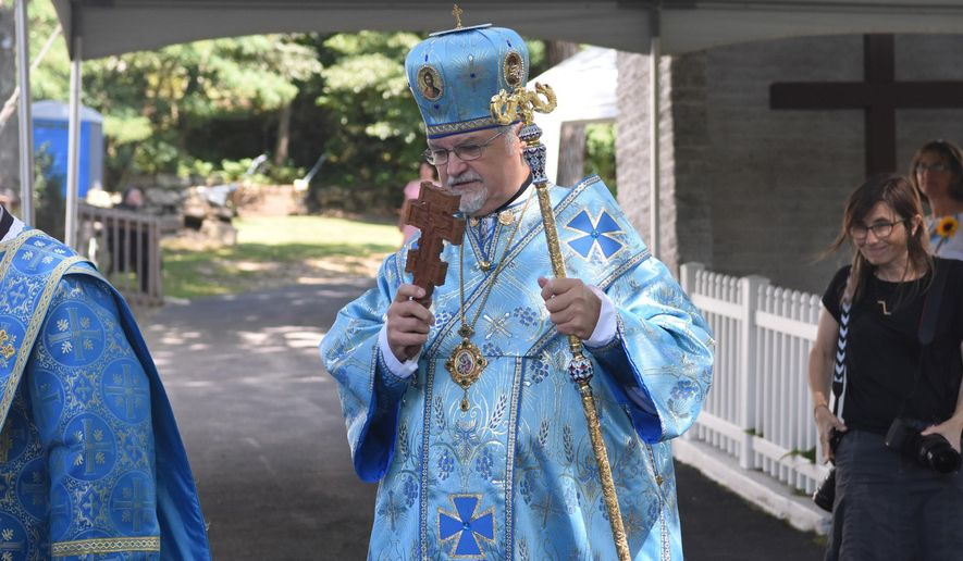 Most Reverend Stefan Soroka, archbishop of the Ukrainian Catholic Archeparchy of Philadelphia and Metropolitan of Ukrainian Catholics in the United States,  blesses those gathered outside of the Assumption of the Blessed Virgin Mary Ukrainian Catholic Church as they watch the procession going into the church for the Divine Liturgy at noon in Centralia, Pa., Sunday, Aug. 28, 2016. The church has been named a holy site of pilgrimage by Major Archbishop Sviatoslav Shevchuk and hosted its first pilgrimage on Sunday. (Jacqueline Dormer/Republican-Herald via AP)