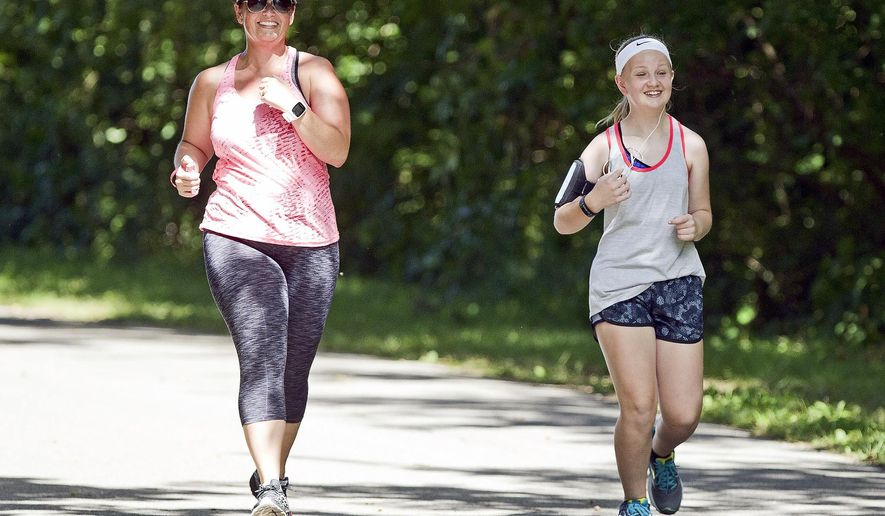 In this Aug. 29, 2016 photo, April Sinnock and her daughter Camryon, 12, run  along a path at Moorman Park in Quincy, Ill. Sinnock is helping get a YMCA running club for kids off the ground in Quincy. (Jake Shane/The Quincy Herald-Whig via AP)