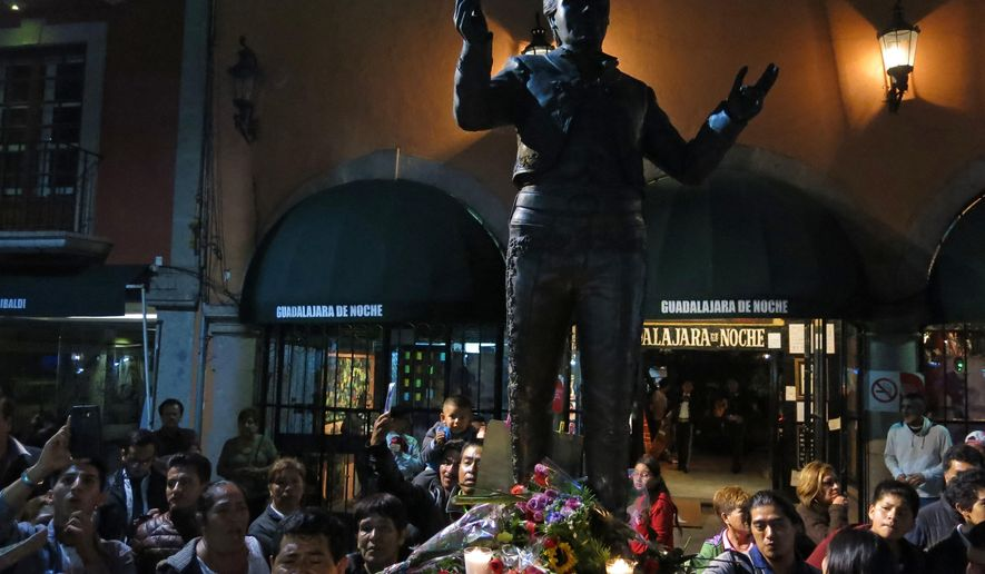 People gather around a statue depicting Mexican superstar songwriter and singer Juan Gabriel in Mexico City's Garibaldi plaza, Sunday Aug. 28, 2016. Juan Gabriel's publicist told The Associated Press that he died at 11:30 a.m. in his home in California. The singer, who was born Alberto Aguilera Valadez on Jan. 7, 1950, wrote his first song at age 13 and went on to compose more than 1,500 songs making him Mexico's leading singer-songwriter and top-selling artist with sales of more than 100 million albums. (AP Photo/Berenice Bautista)