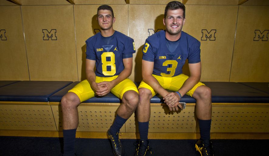 FILE - This Aug. 7, 2016 file photo shows Michigan quarterbacks John O'Korn (8) and Wilton Speight (3) sitting for a photo in the locker room during the NCAA college football team's preseason media day at Michigan Stadium in Ann Arbor, Mich. Jim Harbaugh is expected to release a depth chart, showing who will start for No. 7 Michigan in its opener against Hawaii and all eyes will be on the pecking order at quarterback. (AP Photo/Tony Ding, file)