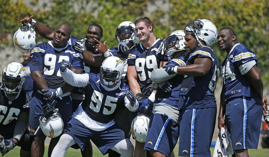 San Diego Chargers NFL football player Joey Bosa (99) is surrounded by defensive teammates who want their photo taken with Bosa at his first practice since agreeing to a four year contract,  Tuesday, Aug. 30, 2016, in San Diego. (AP Photo/Lenny Ignelzi)