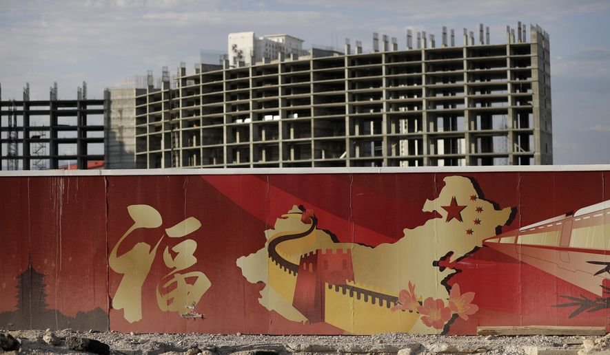 In this Friday, Aug. 26, 2016, photo, a wall with symbols of China partially blocks the view of the Resorts World property in Las Vegas. The Asian-themed casino property is projected to open in 2019. (AP Photo/John Locher)