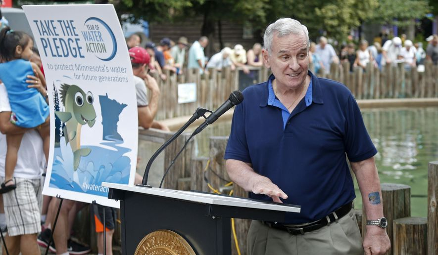 Minnesota Gov. Mark Dayton acknowledges young fair goers after speaking near the fish pond at the State Fair, Tuesday, Aug. 30, 2016 in Falcon Heights, Minn., Dayton is asking Minnesotans to take a Water Stewardship Pledge, and to rethink how water affects their daily lives and how they use it. He hads a stamp on his left arm signifying that he took the pledge. (AP Photo/Jim Mone)