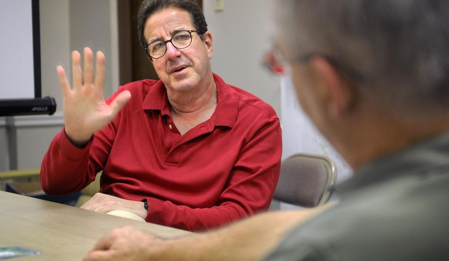 In an Aug. 22, 2016 photo, Fran Feyock, left,  and Richard Schroeder both members of the Association of Licensed Battlefield Guides at Gettysburg, talk with a reporter Dave Sutor at the Tribune-Democrat offices in Johnstown. This summer, both passed Association of Licensed Battlefield Guides exams, meaning they are among the few individuals accredited to give tours of the historic site where Union and Confederate forces clashed in the bloodiest and one of the most important Civil War battles.  (Thomas Slusser/Tribune-Democrat via AP)