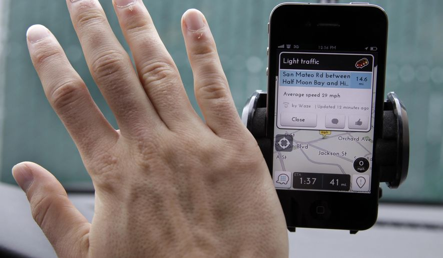 FILE- In this March 15, 2012, file photo, Ben Gleitzman waves his hand over a traffic and navigation app called Waze on his Apple iPhone in a Menlo Park, Calif., parking lot during a demonstration showing traffic conditions on the display. Google is set to expand a San Francisco carpooling program that could morph into a showdown with its one-time ally, the popular ride-hailing service Uber. The program allows anyone using the Waze app to offer a ride to a limited pool of people trying to get to work or home. (AP Photo/Paul Sakuma, File)