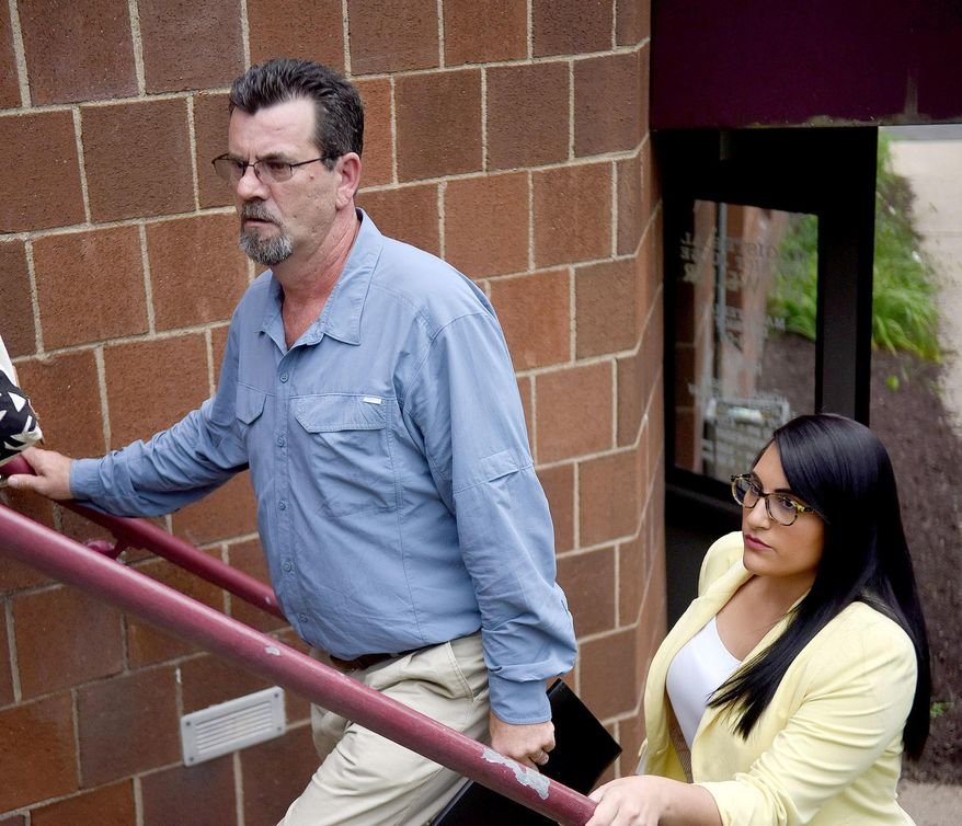 In this July 26, 2016 photo,  Kevin Lee Ewing, left, leaves with one of his attorneys after a preliminary hearing with District Judge Jay Weller in Canonsburg, Pa. Ewing's case will go to court on charges including kidnapping and aggravated assault. Ewing, free on bond while awaiting trial on charges he abducted and beat his wife while holding her captive for nearly two weeks earlier this summer, kidnapped her again Tuesday, Aug. 30, 2016, and is on the run, state police said.  (Katie Roupe /Observer-Reporter via AP)