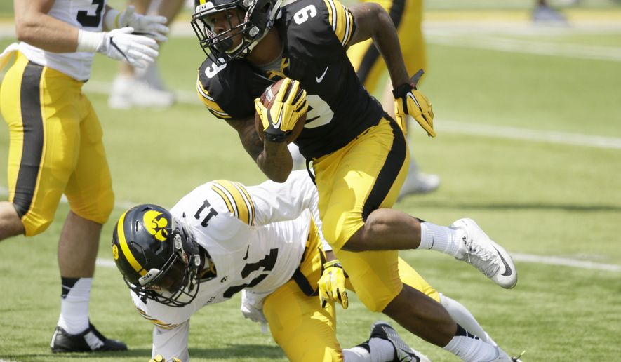 FIEL - In this Saturday, April 23, 2016 file phot, Iowa wide receiver Jerminic Smith (9) runs from defensive back Michael Ojemudia (11) after making a reception during the team's NCAA college football spring game in Iowa City, Iowa. Iowa coach Kirk Ferentz will typically play veterans he trusts over youngsters who might have more potential.(AP Photo/Charlie Neibergall, File)