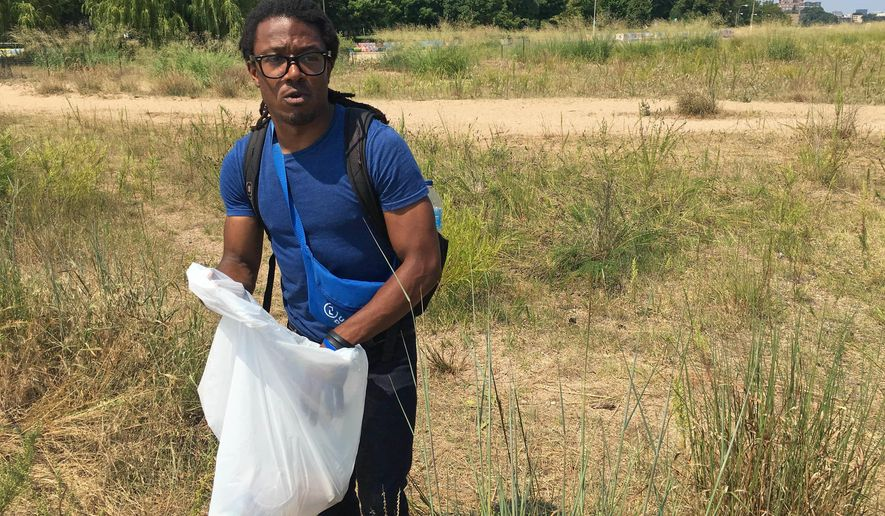 In this Aug. 10, 2016 photo, Kenneth Pettigrew, a Pokemon Go player, has organized with other players to clean up at the Loyola Dunes area on Chicago's lakeshore. The protected dunes have become a popular hot-spot for Pokemon Go players. The heavy foot-traffic has raised concerns about environmental damage and inspired an Illinois state lawmaker to propose legislation to require removal of certain places from the game. The bill is one of the first of its kind in the US. (Jacob Wittich/Sun Times via AP) /Chicago Tribune via AP)