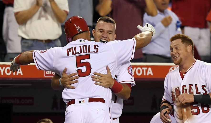 Los Angeles Angels' Albert Pujols, left, is congratulated by Mike Trout, center, as Kole Calhoun watches during the first inning of a baseball game against the Cincinnati Reds, Monday, Aug. 29, 2016, in Anaheim, Calif. (AP Photo/Mark J. Terrill)