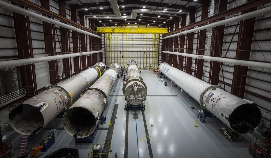 This June 6, 2016 photo made available by SpaceX shows recovered Falcon rocket boosters in a hangar at the Kennedy Space Center on Merritt Island, Fla. The company says it can save considerable time and money by reusing the big, expensive parts. (SpaceX via AP)