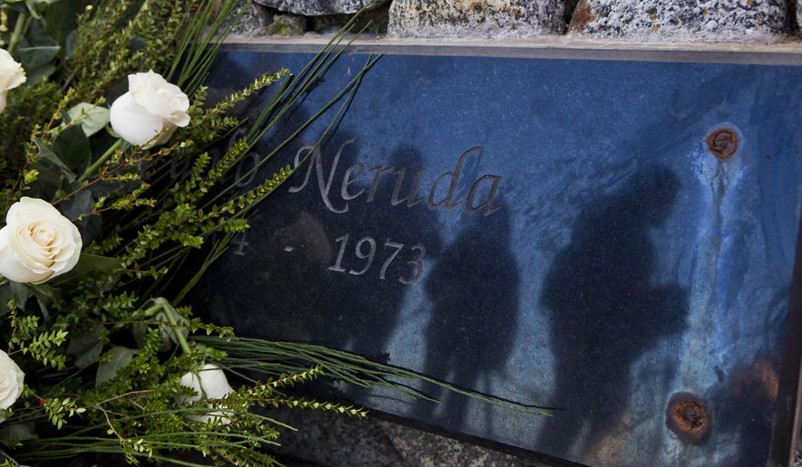 Journalists are reflected on the tombstone of Chile's Nobel Prize-winning poet Pablo Neruda after he was reburied at his home, now a museum, on Isla Negra, Chile, Tuesday, April 26, 2016. Neruda's body was exhumed in 2013 for a fourth time in an effort to clear up four decades of suspicion about how the poet died in the days after Chile's military coup. The results of the analysis will be delivered on May 5. (AP Photo/Esteban Felix)