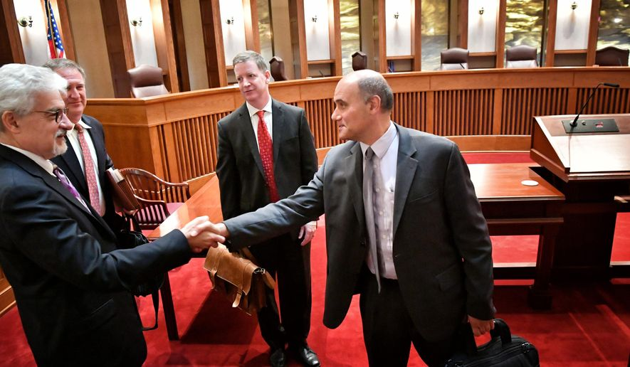 Jordan Kushner, right, the attorney representing the Committee for Professional Policing, which drafted the police insurance plan, shakes hands with Tim Skarda, Minneapolis assistant city attorney, who opposed him after arguing their positions in front of the state's Supreme Court, Tuesday, Aug. 30, 2106, in St. Paul, Minn. The Minnesota Supreme Court heard arguments in two high-profile citizen proposals angling to get on the Minneapolis ballot this November. One that would boost the city's minimum wage to $15 per hour and another that would require police officers to carry professional liability insurance. (Glen Stubbe/Star Tribune via AP)