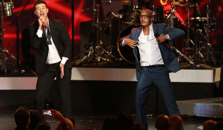 "Robin Thicke, left, and T.I. perform ""Blurred Lines"" at the Grammy Nominations Concert Live! at the Nokia Theatre L.A. Live in Los Angeles in this Dec. 6, 2013 file photo. More than 200 musicians filed a brief with the Ninth Circuit Court of Appeals on Tuesday, Aug. 30, 2016, to express concern about the ruling last year in a case brought by the children of Marvin Gaye, who sued for copyright infringement claiming ""Blurred Lines"" copied Gaye's hit ""Got to Give it Up.""  (Photo by Matt Sayles/Invision/AP, File) **FILE**"
