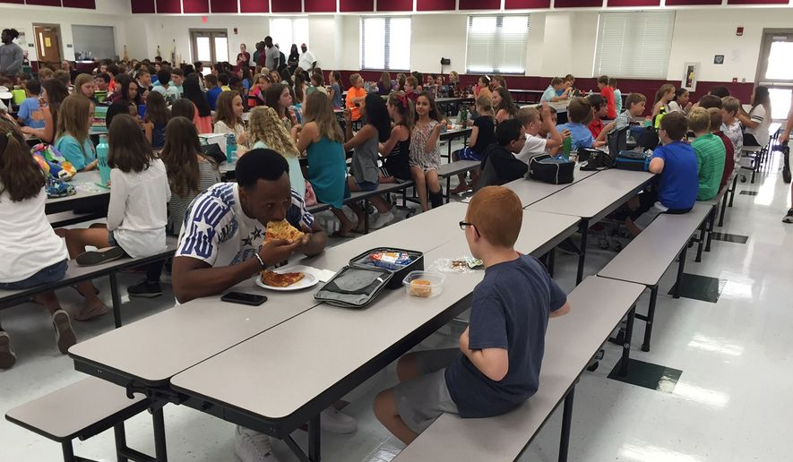 In this Tuesday, Aug, 30, 2016 photo provided by Michael Halligan, Florida State University wide receiver Travis Rudolph has lunch with Bo Paske at Montford Middle School in Tallahassee, Fla. A small gesture of kindness by Rudolph sent tears streaming down the face of the sixth-grader's mother, Leah Paske, who shared her gratitude on Facebook Tuesday afternoon after seeing a picture of Rudolph sharing lunch with her son Bo in his middle school cafeteria. (Michael Halligan via AP)