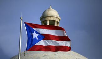 In this July 29, 2015, file photo, the Puerto Rican flag flies in front of Puerto Rico's Capitol as in San Juan, Puerto Rico. (AP Photo/Ricardo Arduengo, File)