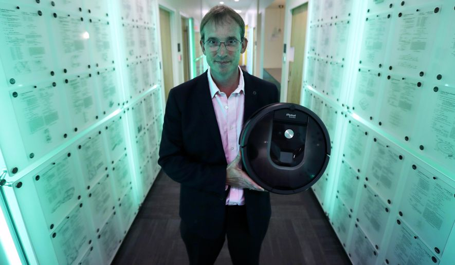 In this Thursday, Aug. 25, 2016, photo, iRobot co-founder and CEO Colin Angle is illuminated in blue-green light while holding a Roomba vacuum in a hallway decorated in patents the company owns, at their headquarters in Bedford, Mass. Angle is transitioning the company from military projects to household robots. (AP Photo/Charles Krupa)