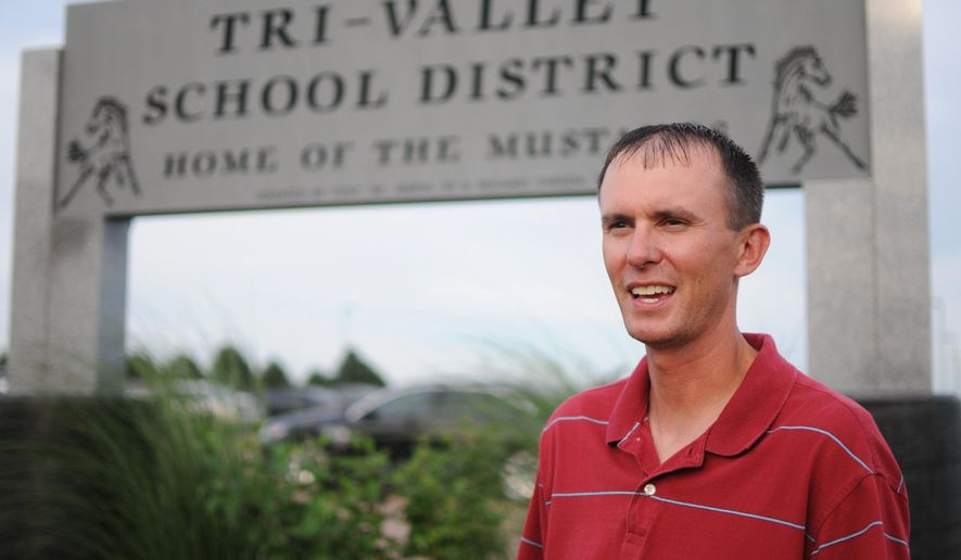 In this Monday, Aug. 29, 2016 photo, Ryan Fods, the mayor of Colton, S.D., speaks about the school sentinel policy outside of Tri-Valley School District in Colton. Fods has children in the district and supports the armed sentinel program. The law requires anyone acting as a school sentinel to successfully complete training designed by the same commission that sets training standards for law enforcement officers. It includes firearms proficiency, first aid, use of force and weapons retention and storage. (AP Photo/James Nord)