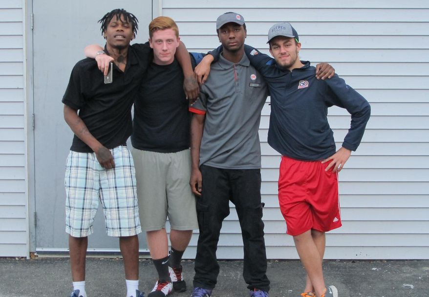 In this Aug. 9, 2016 photo, James Edwards, right, poses for a photo with, from left, fellow residents Dujour Rice, Brandon David and Tyren Jones outside the Plymouth Crossroads youth homeless residence in Lancaster, N.Y., as Edwards prepared to leave for college. Edwards completed high school while homeless after receiving bus transportation from the residence to his former school under a provision that is being expanded under the new education law. (AP Photo/Carolyn Thompson)