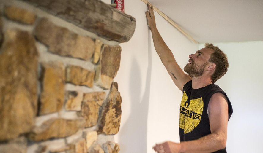 Reed Chambers mocks up trim inside his family's basement Monday, Aug. 22, 2016, in preparation for a September 1 move-in of a local family being evicted from the Virginian Village apartments in Jackson, Wyo. (Ryan Dorgan/Jackson Hole News&Guide via AP)