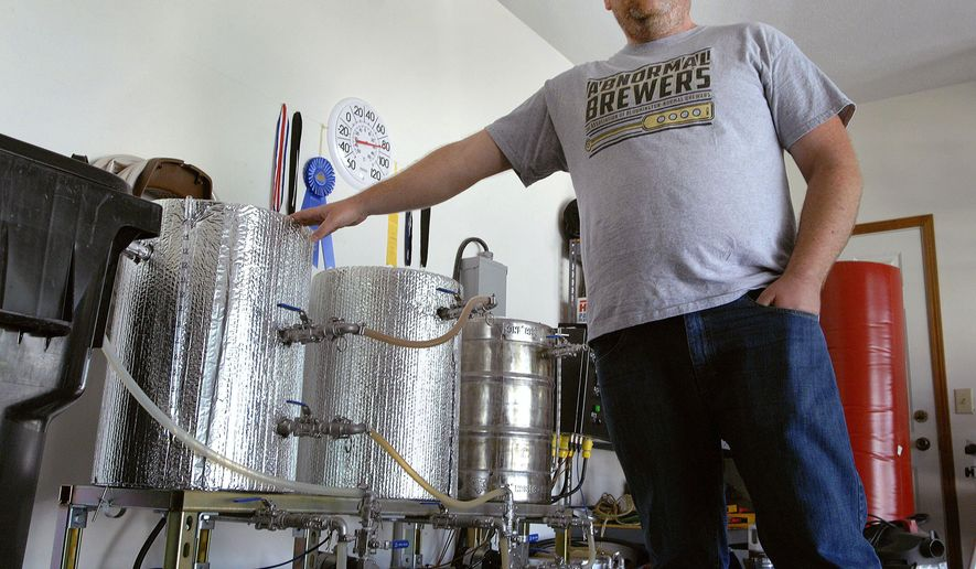 In this Aug. 10, 2016 photo, Kevin O'Leary, explains how his home brewery  works, in his garage in Normal, Ill. The stainless steel tanks and fittings can manage to brew a 10 gallon custom recipe that he personally designs. More than 1.2 million people brew their own beer at home in the United States, according to the American Homebrewers Association. (David Proeber/The Pantagraph via AP)