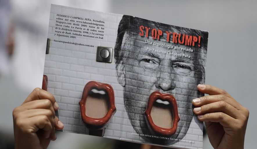 """A demonstrator protesting Donald Trump's meeting with the Mexican president holds up a book jacket with the title; """"Stop Trump!"""" during a morning protest at the Angel of Independence Monument that drew just a handful of people, in Mexico City, Wednesday, Aug. 31, 2016. Donald Trump is making a quick trip to Mexico on Wednesday, meeting with the president of a nation he derided at the start of his White House campaign as a source of rapists and criminals coming to the U.S.(AP Photo/Rebecca Blackwell)"""