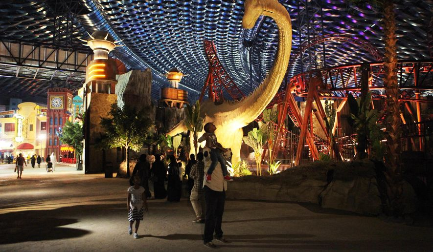 A man puts a small boy on his shoulders to look at an animatronic dinosaur at the IMG Worlds of Adventure amusement park in Dubai, United Arab Emirates, on Wednesday, Aug. 31, 2016. The IMG Worlds of Adventure indoor theme park opened Wednesday in Dubai, hoping to draw thrill seekers to its air-conditioned confines. (AP Photo/Jon Gambrell)